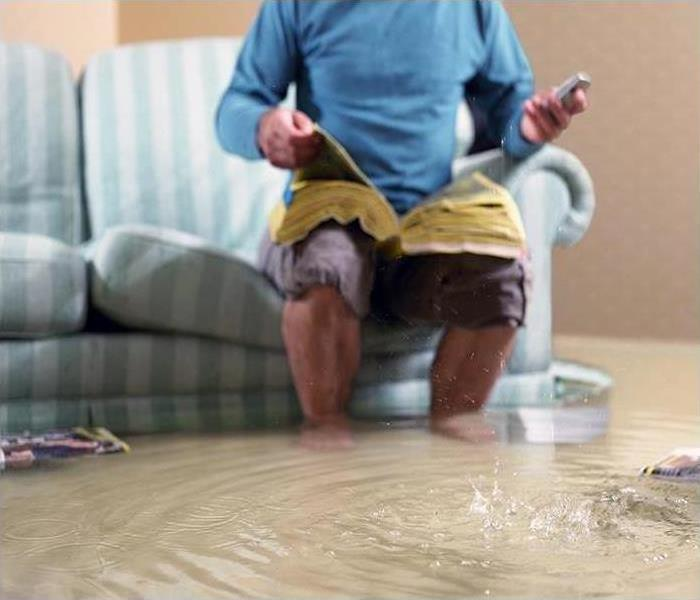 Man sitting on sofa while water rises.
