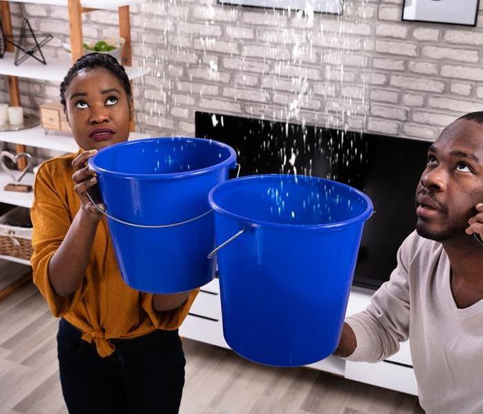 A man and woman holding buckets catching water falling from the ceiling.