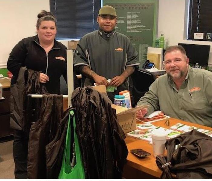 Three SERVPRO employees in a room smiling at the camera.